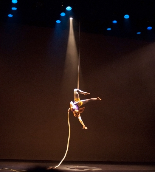 Shot of a woman dancing whilst hanging on a rope.